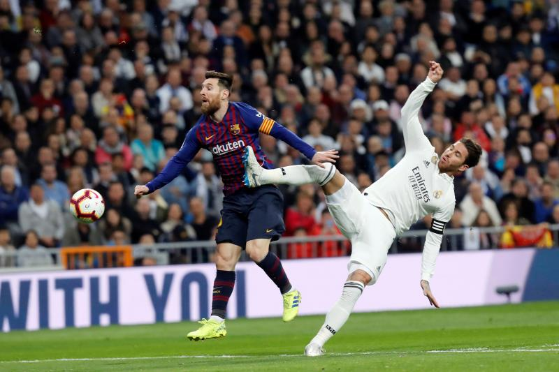 Leo Messi y Sergio Ramos pelean por un balón.