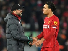 Jurgen Klopp (left)will be without Virgil van Dijk (right)for a lengthy period. AFP