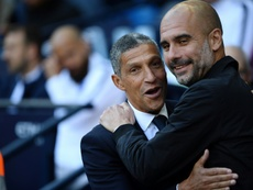 Hughton pictured with Pep Guardiola. AFP