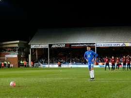 Lee Angol, del Peterborough, va a lanzar el último penalti de la tanda, que detendría Foster. AFP