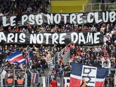 PSG supporters with the banner in respect to the fire.  AFP
