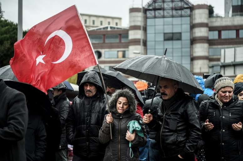 People hold a Turkish flag at the site of the December 10 blasts near Besiktas Vodafone Arena. AFP