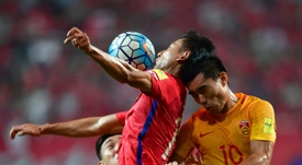 South Koreas Ji Dong-Won (L) fights for the ball with Chinas Zheng Zhi (R). AFP