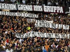 Metz supporters hold banners that got their match with PSG halted for three minutes. AFP