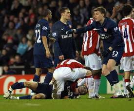 Stoke city's Glenn Whelan attends to Arsenal's Aaron Ramsey in 2010. AFP