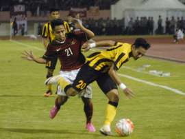 Indonesias Andik Vermansyah (back) challenges Mohd Azrif Nasrulhaq Badrul Hisham of Malaysia during their friendly football match in Solo on September 6, 2016