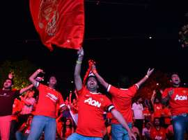 Supporters of Manchester United cheer during a match in New Delhi on May 17, 2015