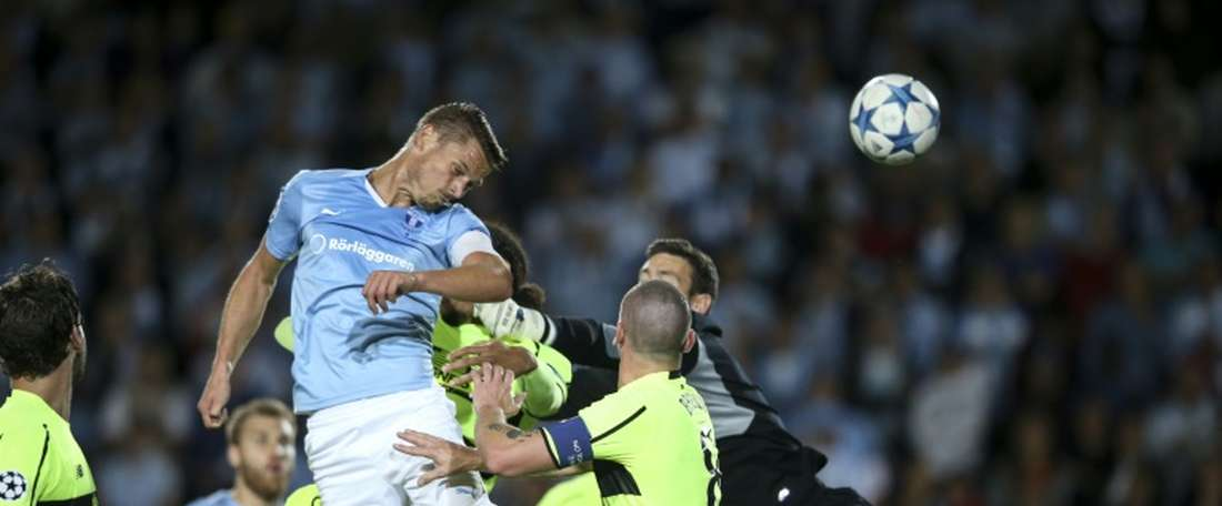 Malmos Markus Rosenberg (L, center) heads the ball to score the opening goal past Celtics goalkeeper Craig Gordon (R) and Celtics Scott Brown (2nd R) during the UEFA Champions League play-off second leg football match in Malmo on August 25, 2015
