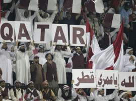 Qatari fans hold banners to show their support for their national team during the group B 2014 World Cup Asian qualifying football match between Qatar and South Korea in Doha on June 8, 2012