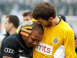 Partizan Belgrades goalkeeper Filip Kljajic (right) hugs Everton Luiz as he leaves the field. AFP