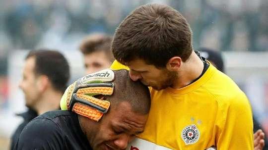 Partizan Belgrades goalkeeper Filip Kljajic (right) hugs Everton Luiz as he leaves the field. AFP