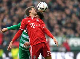 Bremen's Thomas Delaney and Bayern Munich's Thomas Mueller try to head the ball. AFP