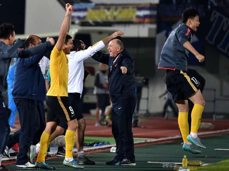Chinas Guangzhou Evergrande head coach Luiz Felipe Scolari (C) celebrates with team players after the AFC Champions League semi-final football match against Japans Gamba Osaka on October 21, 2015