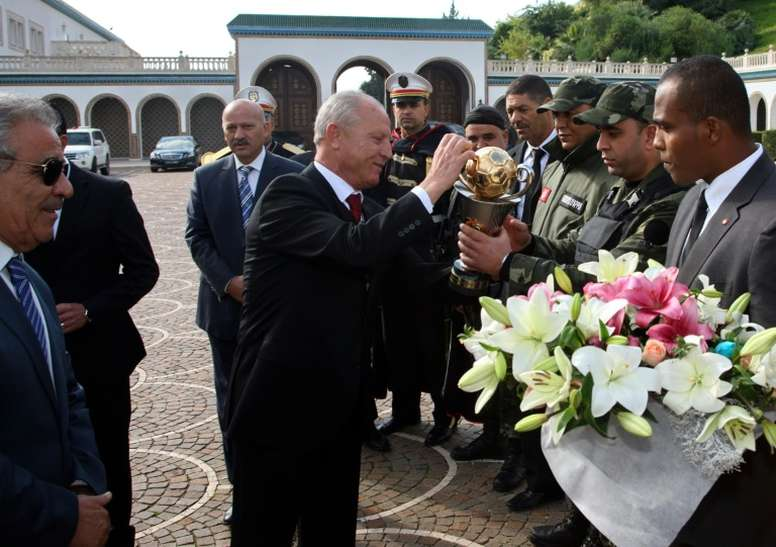 Etoile du Sahels club President Ridha Charfeddine (C) offers flowers before giving the Confederation of African Football trophy to presidential guards on December 2, 2015 at Carthage Palace in Tunis