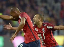 Lilles French defender Djibril Sidibe (L) celebrates with Lilles Moroccan midfielder Mounir Obbadi during the French L1 football match between Lille and Montpellier on October 2, 2015 in Villeneuve dAscq, northern France