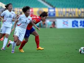 Lee Hyun Young (right) of South Korea fights for the ball with North Koreas Yun Song Mi (centre) during their womens East Asian Cup match at in Wuhan on August 8, 2015