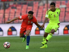 Chiles Alexis Sanchez (L) fights for the ball with Venezuelas Renzo Zambrano