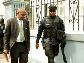 Former FIFA vice president Jack Warner (L) is escorted by a police officer to the Port-of-Spain Magistrates court in Trinidad, for an extradition hearing on July 27, 2015