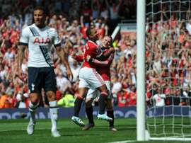 Manchester Uniteds Memphis Depay (2nd right) celebrates with Wayne Rooney (right) after United take the lead due to an own goal from Tottenham Hotspurs Kyle Walker at Old Trafford on August 8, 2015