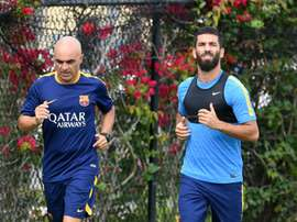 Barcelonas new player Arda Turan (R) runs with a trainer during a light training session at the StarHub Stadium in Carson, California, on July 20, 2015