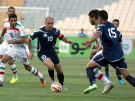 Guams player Jason Cunliffe (C) is challenged by Iranian players during a qualifying match for the 2018 FIFA World Cup at the Azadi stadium in Tehran on September 3, 2015