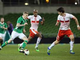 Republic of Irelands midfielder James McClean (L) runs with the ball as Switzerlands midfielder Gelson Fernandes and defender Timm Klose (R) defend during the friendly football match in Dublin on March 25, 2016