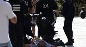 French riot police attend to England fan Andrew Bache as he lies injured. AFP