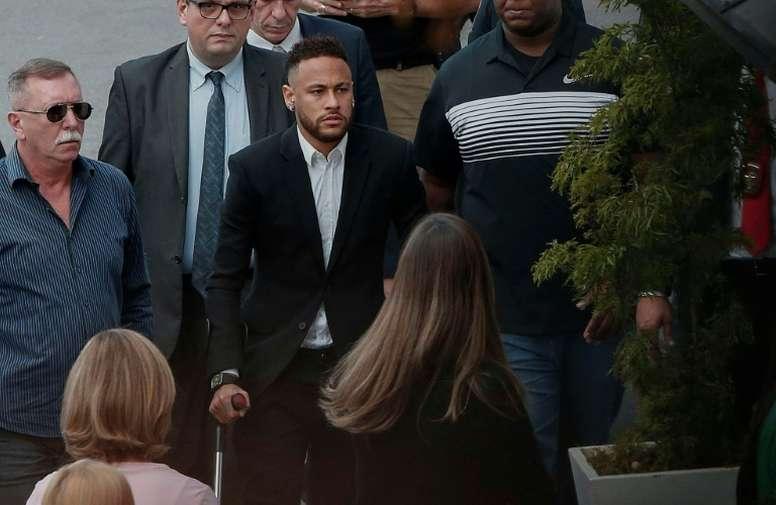 Neymar, arropado al llegar a comisaría. AFP