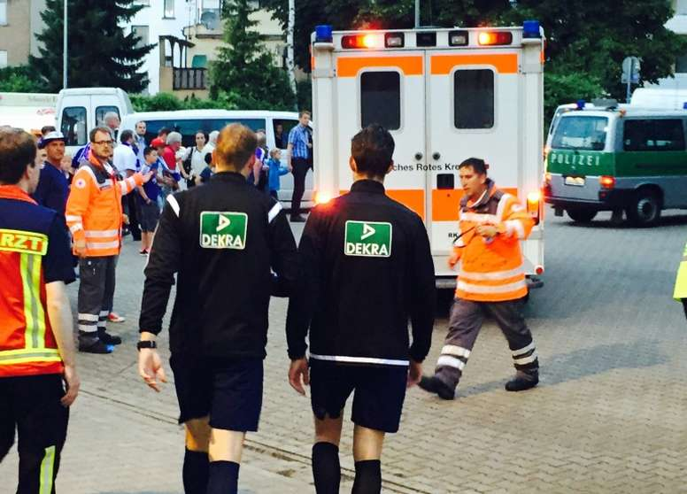 Martin Petersen (centre left) makes his way to an ambulance for a check up after being hit by a lighter Osnabrucks German Cup game against Leipzig in Osnabruck on August 10, 2015