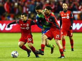 Sebastian Giovinco (L) and Jonathan Osorio of Toronto FC fight off a challenge from Cristian Roldan of the Seattle Sounders during the 2017 MLS Cup Final