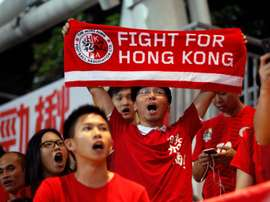 Hong Kong football fans cheer for their team during the World Cup qualifier against China at Hong Kongs Mong Kok Stadium on November 17, 2015