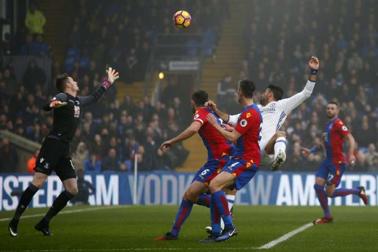 Diego Costa (2R) watches the ball after jumping to head and score against Crystal Palace. AFP