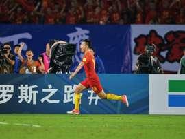 Gao Lin celebrates scoring a goal against Uzbekistan. AFP