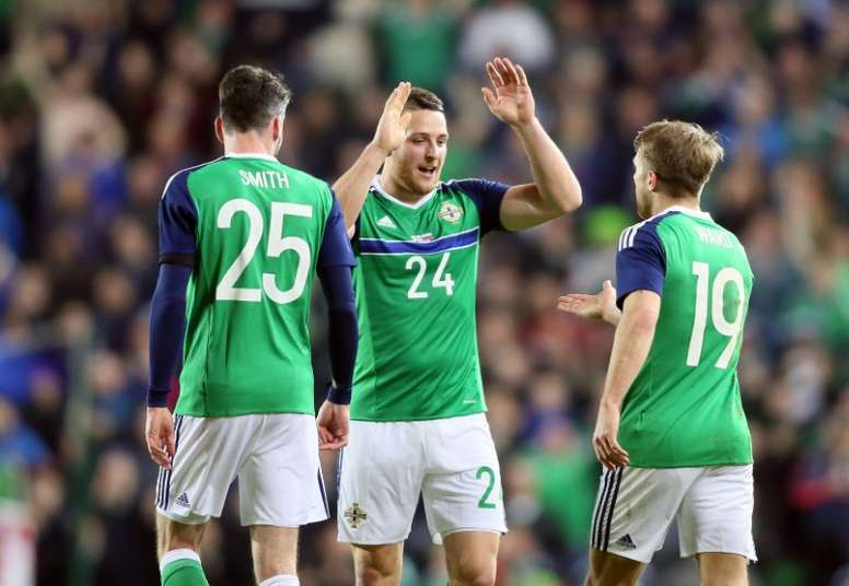 Northern Irelands striker Conor Washington (C) celebrates with defender Michael Smith (L) and striker Jamie Ward (R) after scoring the opening goal of the international friendly football match against Slovenia on March 28, 2016.