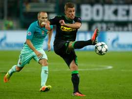 Thorgan Hazard (R) kicks the ball in front of Barcelona midfielder Andres Iniesta. AFP