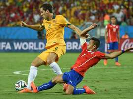 Australias Matthew Spiranovic (L) fights for the ball with Chiles Alexis Sanchez during their 2014 FIFA World Cup group match