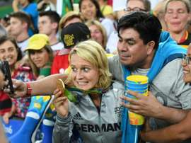 A Germany player holds up her gold medal as she poses for a selfie with a fan. AFP