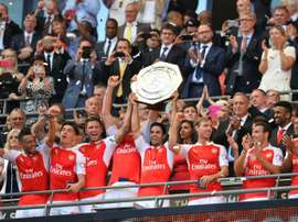 Arsenals midfielder Mikel Arteta (C) lifts the trophy as Arsenal players celebrate after beating Chelsea in the FA Community Shield football match at Wembley Stadium in north London on August 2, 2015