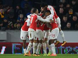 Arsenals midfielder Theo Walcott celebrates with teammates after scoring their third goal during the FA cup fifth round replay football match between Hull City and Arsenal in Kingston upon Hull in north east England on March 8, 2016