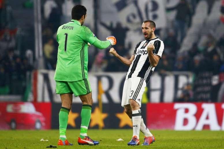 Juventus goalkeeper Gianluigi Buffon (L) celebrates with teammate iorgio Chellini during their game against AS Roma on December 17, 2016 in Turin