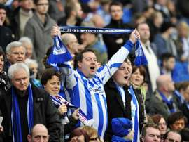 Brighton & Hove Albions fans sing in the crowd ahead of a football match in Brighton. BeSoccer