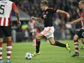 Manchesters Luke Shaw (C) vies with PSV Eindhoven's midfielder Jorrit Hendrix (R) during the UEFA Champions League Group B football match at the Philips stadium in Eindhoven, Belgium on September 15, 2015