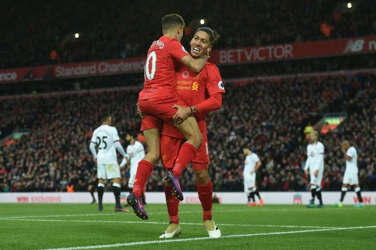 Firmino (R) celebrates a goal with Philippe Coutinho. AFP