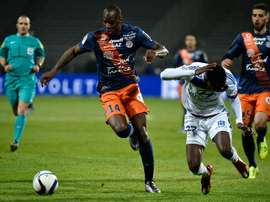 Montpelliers French midfielder Bryan Dabo (L) vies for the ball with Lyons French forward Maxwel Cornet (R) during the French L1 football match at the Gerland Stadium in Lyon, central-eastern France, on November 27, 2015