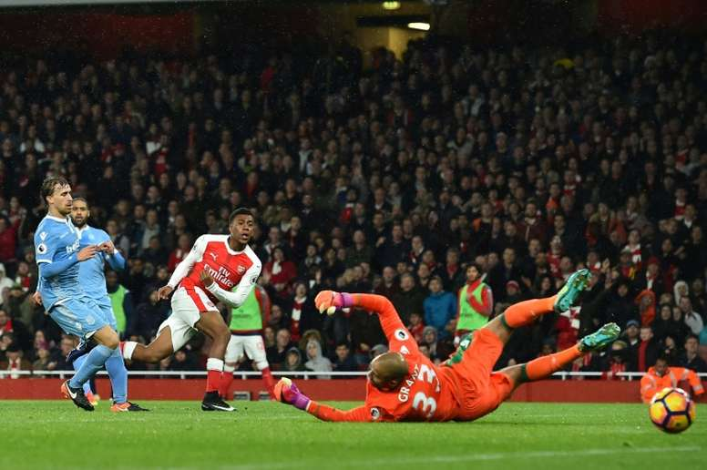 Arsenals Alex Iwobi (3L) shoots and scores past Stoke Citys goalkeeper Lee Grant at the Emirates Stadium in London