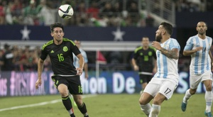 Hector Herrera (L) of Mexico and Nicolas Otamendi of Argentina chase a high ball during a international friendly at AT&T Stadium in Arlington, Texas on September 8, 2015