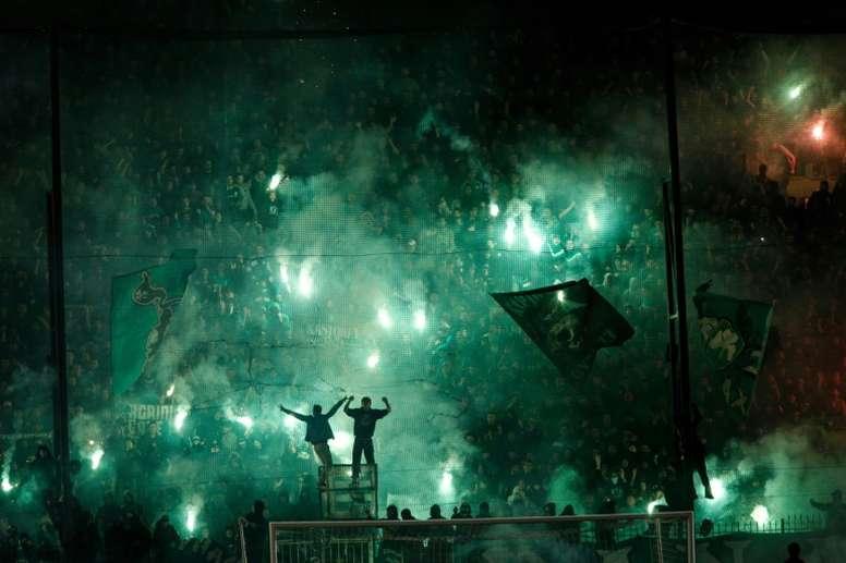 Los hinchas del Panathinaikos iluminan las gradas con bengalas en un partido de la Liga Griega. AFP