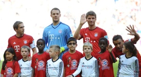 (L-R) Bayern Munichs defender Philipp Lahm, Manuel Neuer and Thomas Mueller stand with migrant children (in red) prior to the German first division Bundesliga football match FC Bayern Munich v FC Augsburg, in Munich on September 12, 2015