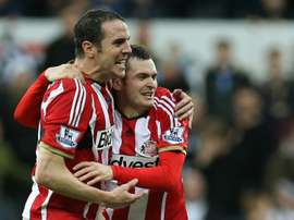 Sunderland captain John OShea (L) celebrates with teammate Adam Johnson at the end of the Premier League match against Newcastle United at St James Park on December 21, 2014
