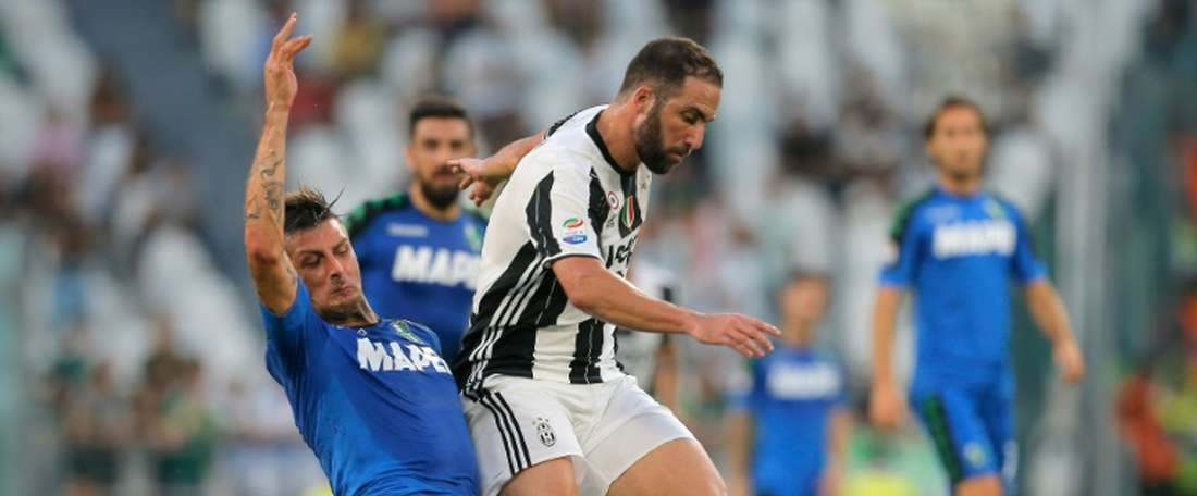 Juventus forward Gonzalo Higuain from Argentina (R) fights for the ball with Sassuolos defender Francesco Acerbi during the Italian Serie A football match Juventus Vs Sassuolo on September 10, 2016